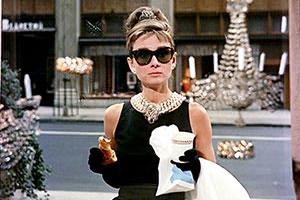 With a danish and coffee in hand, Holly (Audrey Hepburn) taught modern women to chase a chimera and eat on the run.